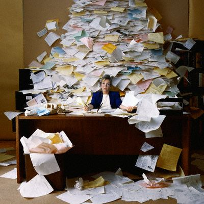 Office Worker with Mountain of Paperwork --- Image by © Royalty-Free/Corbis